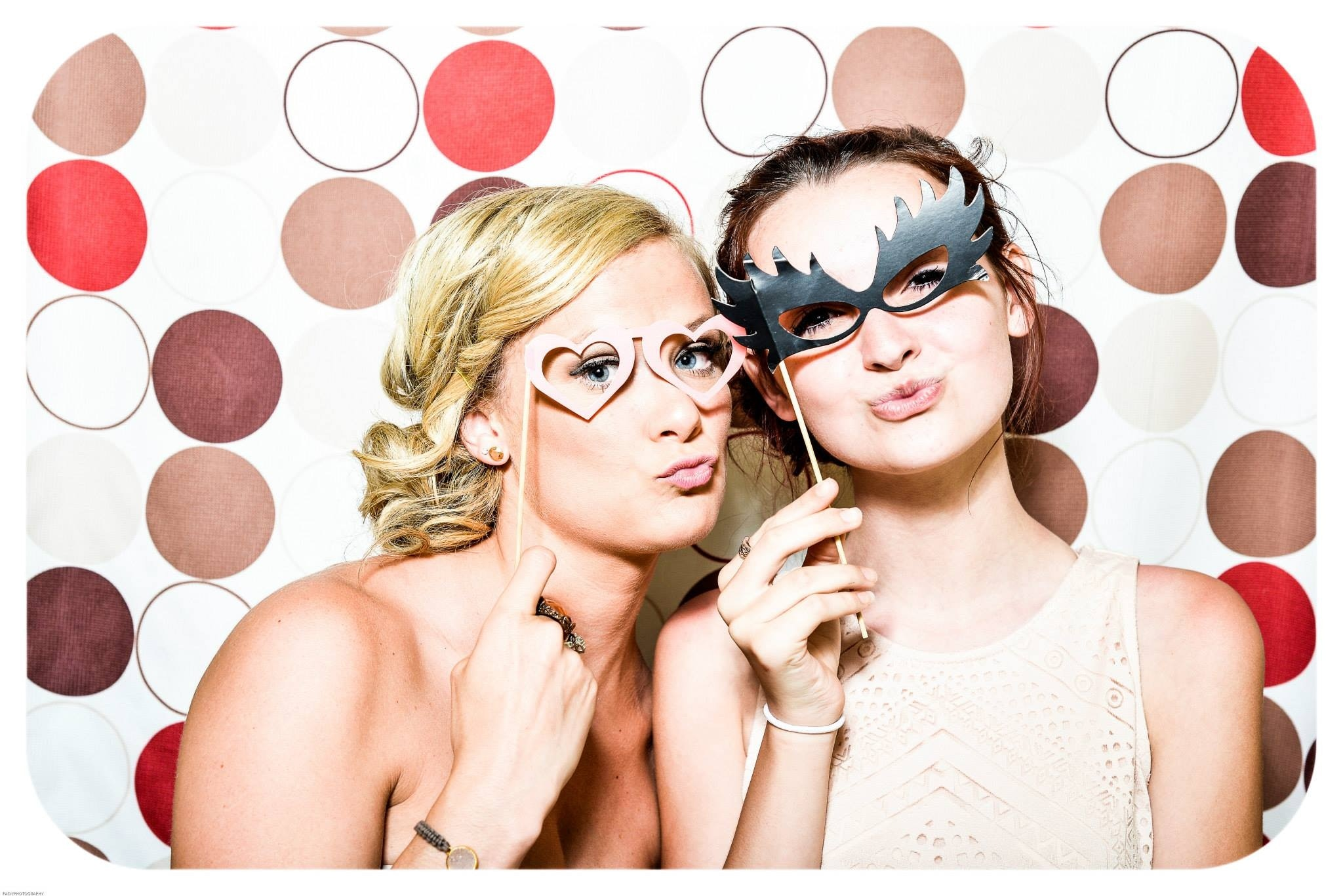 Two women taking picture in photo booth. See our photo booth options.